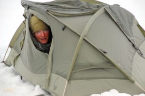 winter camping tent with head poking out tent flap